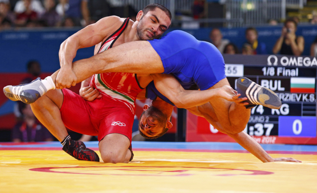 Iran's Sadegh Saeed Goudarzi fights with Bulgaria's Kiril Stoychev Terziev on the Men's 74Kg Freestyle wrestling at the ExCel venue during the London 2012 Olympic Games